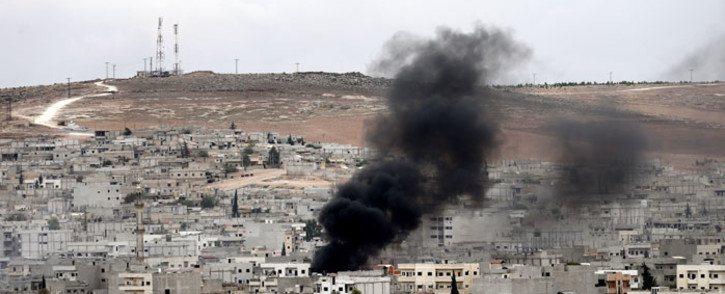 FILE: Smoke rises during armed clashes between Syrian Kurdish fighters and militants from Islamic State in and around the town of Kobane, Syria, as seen from the Turkish side of the border. Picture: AFP.
