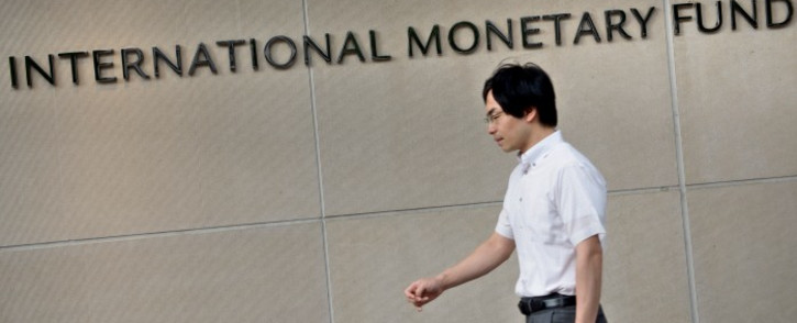 A man walks past the headquarters of the International Monetary Fund (IMF) on 30 June 2015 in Washington, DC. Picture: AFP.