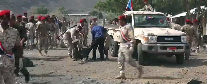 This AFPTV screengrab from a video made on 1 August 2019, shows Yemeni security forces carrying a body at the scene of a missile attack on a military camp west of Yemen's government-held second city Aden. Picture: AFP