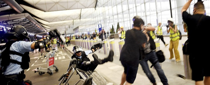 Police scuffle with pro-democracy protestors at Hong Kong's International Airport on 13 August 2019. Picture: AFP