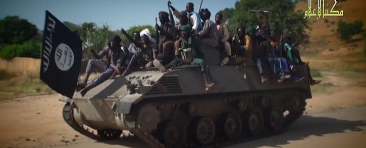 A screengrab taken on 9 November , 2014, from a new Boko Haram video released by the Nigerian Islamist extremist group Boko Haram and obtained by AFP shows Boko Haram fighters parading on a tank in an unidentified town. Picture: AFP.
