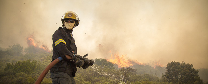 A firefighter prepares to battle a blaze during veld fires in Ocean View. Picture: Thomas Holder/EWN