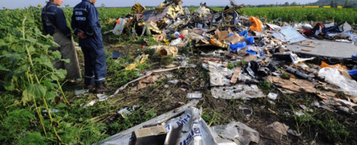 Employees of the Ukrainian State Emergency Service look at the wreckage of Malaysia Airlines flight MH17 two days after it crashed in a sunflower field near the village of Rassipnoe, in rebel-held east Ukraine, on 19 July 2014. Picture: AFP.