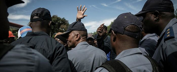 FILE: Police officers surrounded by a crowd. Picture: EWN