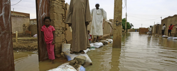 Sudanese residents walk on sandbags to reach their houses along a flooded street in the capital Khartoum's southern neighbourhood of al-Kalakla, on 31 August 2020. Picture: AFP.