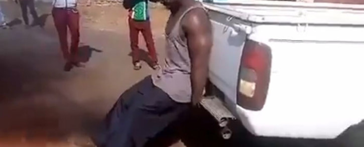 A screengrab of a man stopping a vehicle from reversing. Picture: @LordSizwe/Twitter