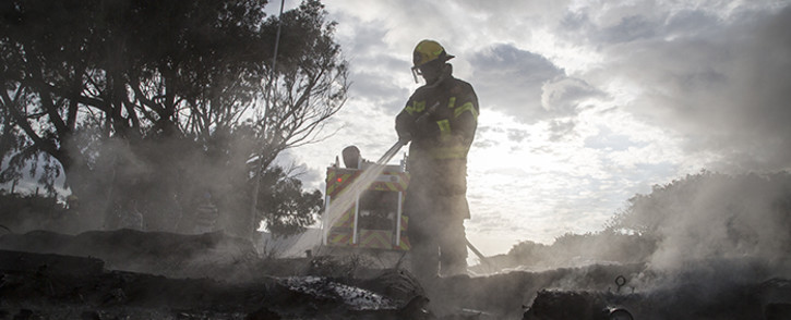 FILE: A Cape Town fire and rescue worker puts out burning debris that was used to barricade Kommetjie Road outside of Masiphumelele township in Cape Town. Picture: Thomas Holder/EWN