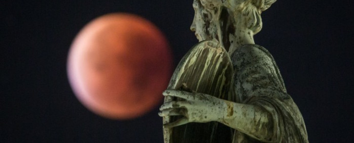 The  supermoon or blood moon seen behind a statue during a total lunar eclipse in Frankfurt am Main, western Germany, on September 28, 2015. Picture: AFP.