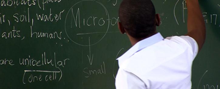 FILE: A teacher draws on the chalkboard while teaching his class. Picture: Reinart Toerien/EWN