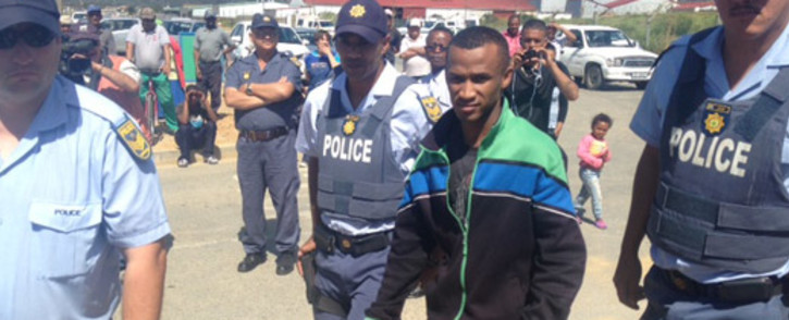Johannes Kana arrives on the scene escorted by police. Pictrure: Renee de Villiers/EWN.