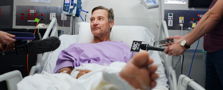 This handout photo received from Princess Alexandra Hospital in Brisbane on 18 September 2019 shows Neil Parker, 54, an Australian bushwalker talking to the media from his hospital bed after he tumbled down a waterfall. Pitcure: AFP