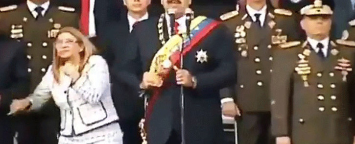 Screengrab taken from a handout video released by Venezuelan Television showing Venezuelan President Nicolas Maduro, his wife Cilia Flores and military authorities reacting to a loud band during a ceremony to celebrate the 81st anniversary of the National Guard in Caracas on 4 August, 2018. Picture: AFP