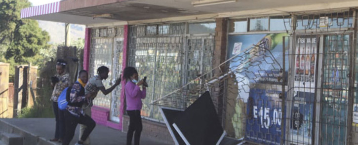 People take pictures of a damaged shop in Mbabane, Eswatini, on 29 June 2021. Demonstrations escalated radically in Eswatini this week as protesters took to the streets demanding immediate political reforms. Picture: AFP
