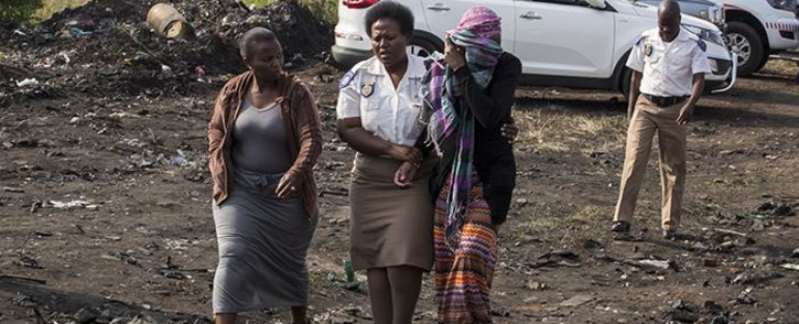 An emotional Nombeko Thole covers her face as she is escorted away from a disused mine near Boksburg where rescue operations for her 5-year-old son were halted on 28 February 2017. Picture: Reinart Toerien/EWN.