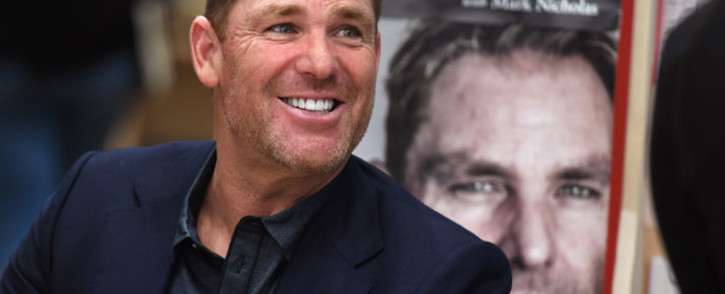 "FILE: Australian cricketing great Shane Warne chats with a customer during a book signing event for his new autobiography titled ""No Spin"", in Melbourne on 19 October 2018. Picture: AFP"