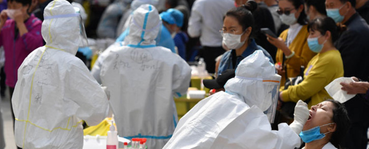 FILE: A health worker takes a swab from a resident to be tested for the COVID-19 coronavirus as part of a mass testing program following a new outbreak of the coronavirus in Qingdao, in China's eastern Shandong province on 13 October 2020. Picture: AFP
