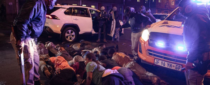 Metro police officers gather people that they have arrested in Hillbrow waiting for vehicles to transport them to cells.  People were made to lie on their stomachs.  Picture: Boikhutso Ntsoko/ Eyewitness News.