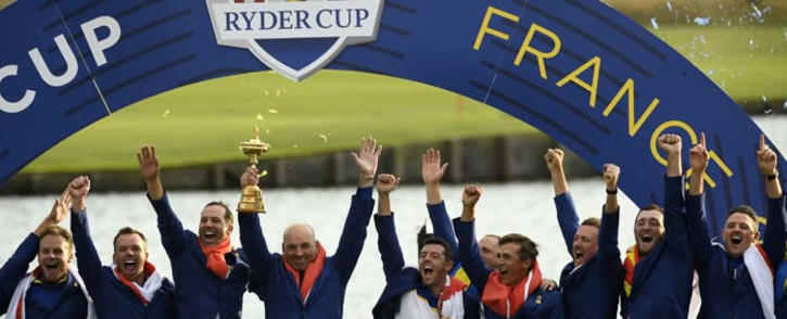 (L-R) Europe's Francesco Molinari, Tommy Fleetwood, Tyrrell Hatton, Paul Casey, captain Thomas Bjorn, Rory McIlroy, Alexander Noren, Thorbjorn Olesen, Ian Poulter, Jon Rahm, Justin Rose and Henrik Stenson celebrate with the trophy after winning the 42nd Ryder Cup at Le Golf National Course at Saint-Quentin-en-Yvelines, south-west of Paris, on 30 September 2018. Picture: AFP
