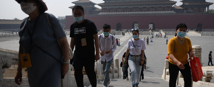 FILE: People wear face masks as a preventive measure against the COVID-19 coronavirus as they walk through the Forbidden City, the former palace of China's emperors, in Beijing on 1 May 2020. Picture: AFP
