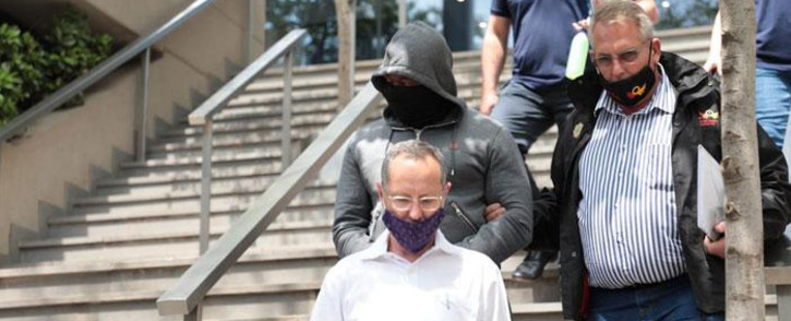 Hawks members escort one of the seven suspects identified for arrest on 30 September 2020 in a case related to a R255m asbestos removal project in Free State. Picture: Abigail Javier/EWN