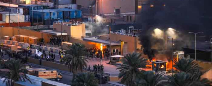 A handout picture received from the US embassy in Iraq on 31 December 2019, shows smoke billowing from a sentry box at an entrance of the embassy in the capital Baghdad, after supporters and members of the Hashed al-Shaabi military network breached the outer wall of the diplomatic mission during a rally to vent anger over weekend air strikes that killed pro-Iran fighters in western Iraq. Picture: AFP.