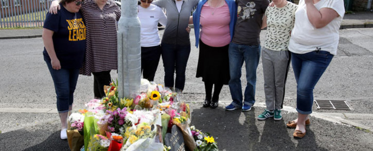 People gather around the floral tributes placed at the scene in the Creggan area of Derry (Londonderry) in Northern Ireland on 20 April 2019 where journalist Lyra McKee was fatally shot amid rioting on 18 April. Picture: AFP