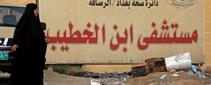 An Iraqi woman walks past a billboard bearing the name of Ibn Al-Khatib Hospital in Baghdad, on 25 April 2021, after a fire erupted in the medical facility reserved for the most severe COVID-19 cases. Picture: AFP