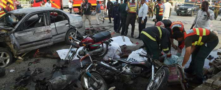FILE: Pakistani rescue workers try to move the bodies of victims at the site of an explosion in Lahore on 24 July 2017. Picture: AFP