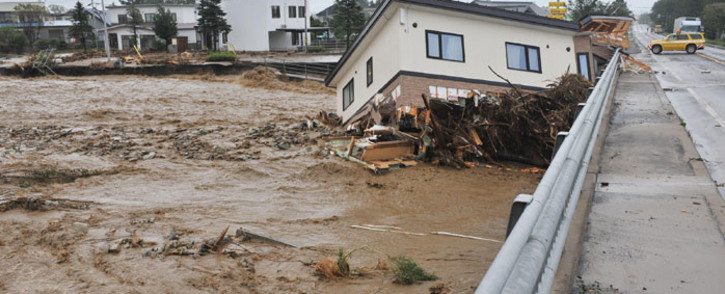 This picture provided by Tokachi Mainichi Newspaper via Jiji Press on 31 August 2016 shows a house swept down a river at the town of Shimizu in Hokkaido prefecture, after Typhoon Lionrock struck overnight. JIJI Press/AFP.