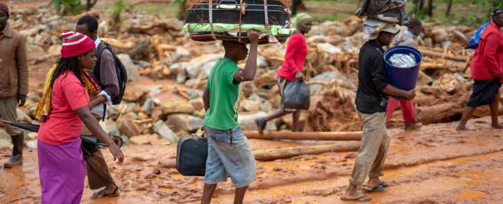 Cyclone survivors leave the Ngangu township with their belongings to Chimanimani Hotel where hundreds are sheltered on 18 March 2019 in Ngangu township Chimanimani, Manicaland Province, eastern Zimbabwe, after the area was hit by the cyclone Idai. Picture: AFP