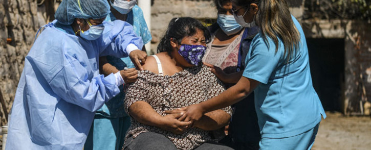Health workers inoculate a woman with a dose of the Pfizer-BioNTech vaccine against COVID-19, in Arequipa, southern Peru, on 2 July 2021. Picture: Diego Ramos/AFP