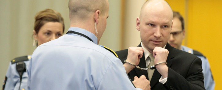 Norwegian mass killer Anders Behring Breivik (R) has his handcuffs removed inside the court room in Skien prison, 16 March, 2016. Picture: AFP.