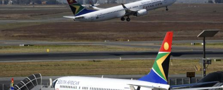 FILE: A South African Airways flight takes off as another one is parked in a bay on the tarmac on 25 May 25 2010 at the OR Tambo International Airport in Johannesburg. Picture: AFP