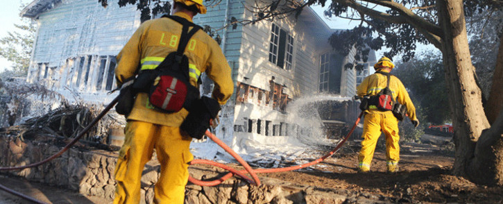 Firefighters spray foam on the remains of a destroyed home in the aftermath of the Holiday Fire on 7 July 2018 in Goleta, California. Picture: AFP