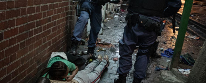Police make people lie on their stomachs after finding them looting inside a store in Hillbrow. Picture: Boikhutso Ntsoko/ Eyewitness News.