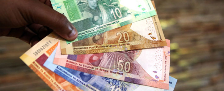A man holds new South African banknotes at the value of ten, twenty, fifty, one hundred and two hundred South African Rand depicting former South African president Nelson Mandela at The South African Reserve Bank (SARB) on 13 July 2018. Picture: AFP