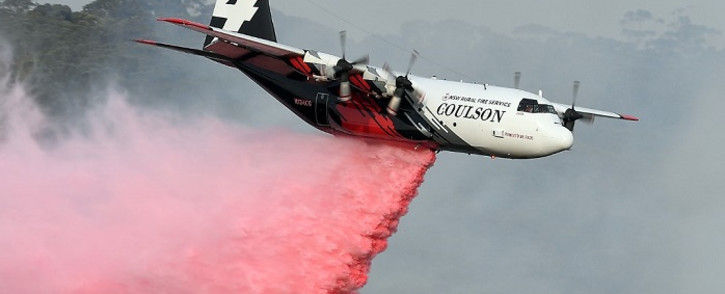 This file photo taken on January 10, 2020 shows a C-130 Hercules plane from the New South Wales Rural Fire Service dropping fire retardent to protect a property during an operation to douse bushfires in Penrose, in Australia's New South Wales state. Picture: AFP
