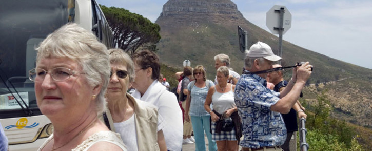 FILE: A group of tourists get off their tour bus at the bottom of the cable station to Table Mountain in Cape Town. Picture: AFP