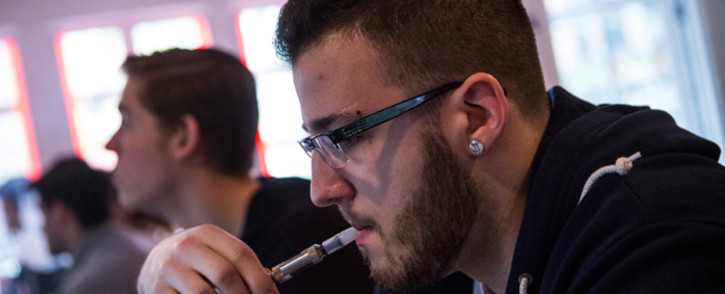 Kyle Stamm, of New York, vapes, or smokes an electronic cigarette, at Henley Vaporium on April 29, 2014 in New York City. A new law that goes into effect today in New York and Chicago subjects electronic cigarettes to the same regulations as tobacco. Picture: AFP.