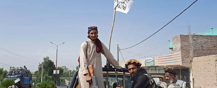 Taliban fighters drive an Afghan National Army (ANA) vehicle through the streets of Laghman province on 15 August 2021. Picture: AFP