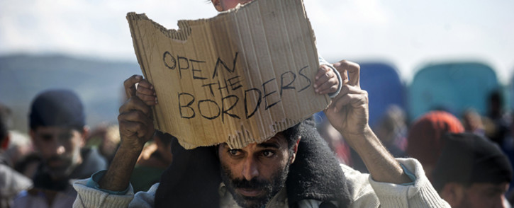 """FILE: A man carries on his shoulders a child holding a banner reading """"Open the borders"""" during a demostration of migrants and refugees protesting behind a fence at the Greek-Macedonian border. Picture: AFP"""
