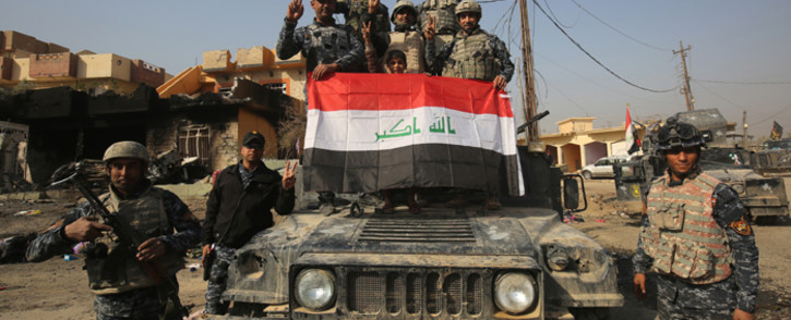 Iraqi forces flash the sign for victory in the Hamam al-Alil area, about 14 kilometres from the southern outskirts of Mosul, on 7 November, 2016 after recapturing it from Islamic State group jihadists. Picture: AFP.