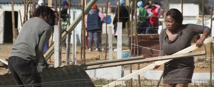 People take their building materials away as workers (not visible), break down uninhabited shacks in Bloekombos, Kraaifontein, in Cape Town on 6 August 2020. Picture: AFP