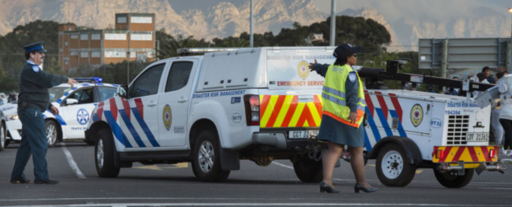 Traffic and police officers direct emergency vehicles into the Rheinmetall Denel munitions facility in Macassar, Cape Town, after an explosion at the facility killed at least 8 people and injured more, on 3 September, 2018. Picture: AFP