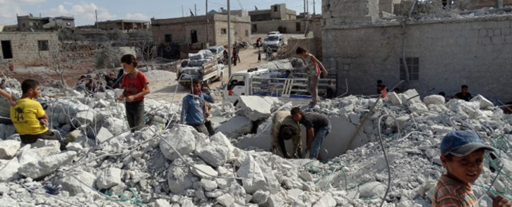 Syrians check a damaged house, reportedly hit by US-led coalition air strikes, in the village of Kfar Derian in the western Aleppo province on 23 September, 2014. Picture: AFP.