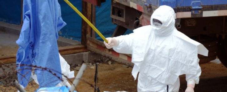 A worker in a Personal Protection Equipment suit (PPE) uses a stick to move garbage inside the high-risk quarantined zone of the John Fitzgerald Kennedy hospital in the Liberian capital Monrovia on 5 September,2014. Picture: AFP.