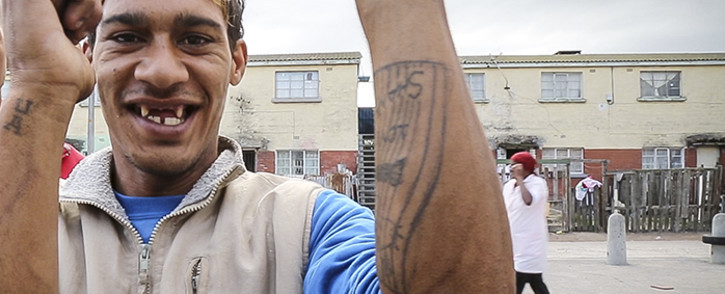 """FILE: A member of the Ugly Americans gang holds up his tattoos or """"tjappies"""", also known as flags, indicating which gang he is from. Picture: Thomas Holder/EWN"""