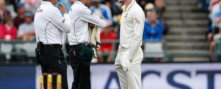 FILE: Australian fielder Cameron Bancroft is questioned by Umpires Richard Illingworth and Nigel Llong during the third day of the third Test cricket match between South Africa and Australia at Newlands cricket ground on 24 March 2018 in Cape Town. Picture: AFP