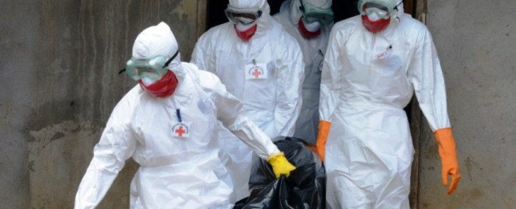 FILE: Medical workers of the Liberian Red Cross, wearing a protective suit, carry the body of a victim of the Ebola virus in a bag on 4 September, 2014 in the small city of Banjol, 30 kilometres of Monrovia. Picture: AFP.