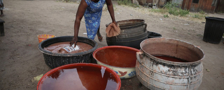 "A woman dips a bucket into a large bucket of ""burukutu"", a locally brewed alcoholic beverage made from the fermented grains of sorghum and millet, in Makurdi, Nigeria, on December 15, 2019. Burukutu, the vinegary alcoholic beverage has been made here for generations from the fermented grains of sorghum and millet and consumed as a traditional alternative to beer. Picture: AFP"